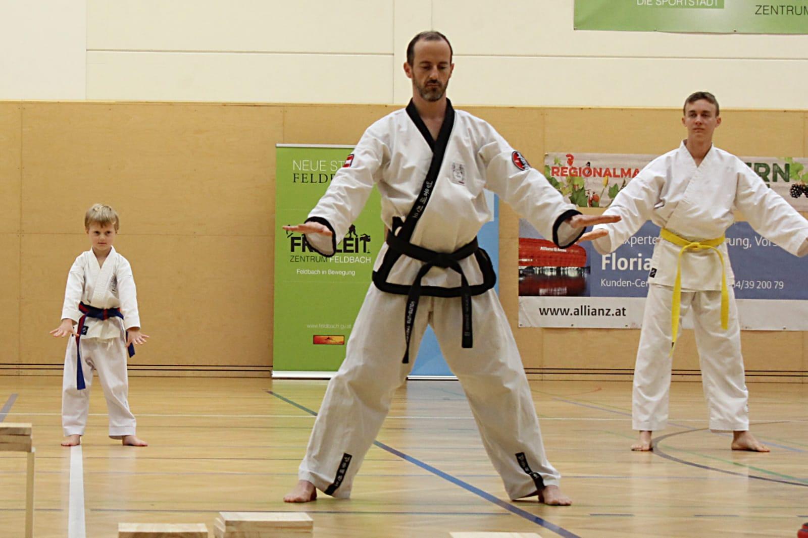 Meister Sandro mit 2 Schülern im Kampfanzug