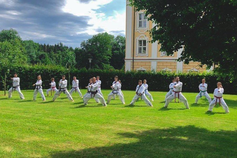 Eine Gruppe von taekwondoschülern trainiert vor dem Kloster Roggenburg.