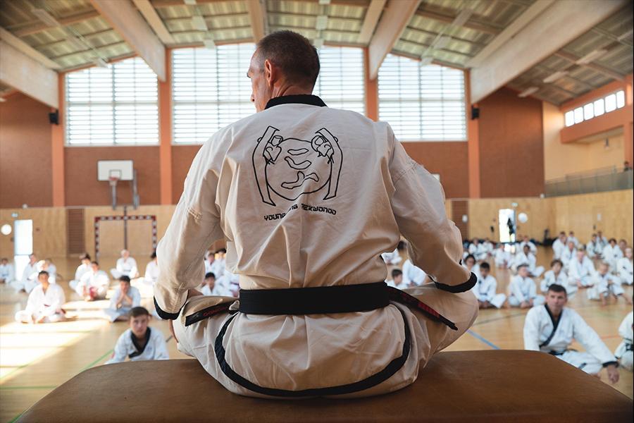 Mann im Taekwondo-Kampfanzug sitzt im Schneidersitz