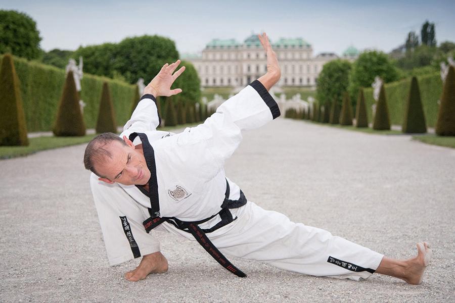 Mann macht Adler-Figur vor dem Schloss Belvedere