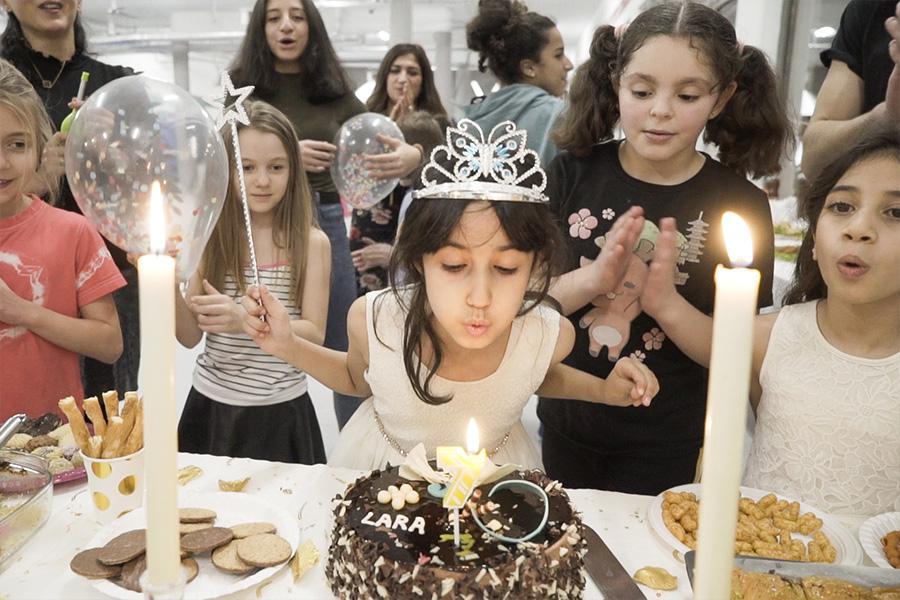 Kindergeburtstagsparty Mädchen mit Krone pustet Kerze auf der Torte aus