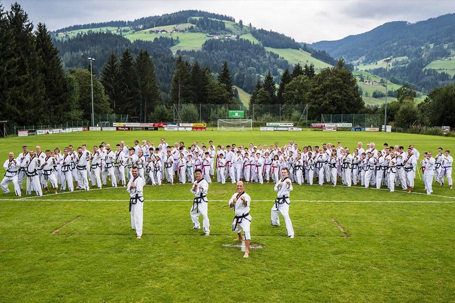 Große Taekwondo Gruppe auf einen Fußballplatz mit Berge im Hintergrund
