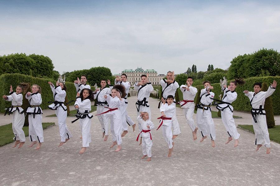 Taekwondo Gruppe springt in der Luft mit Schloss im Hintergrund