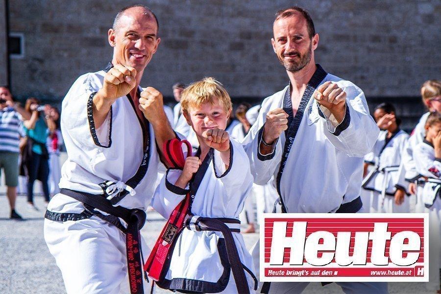 Zwei Männer im Taekwondo-Kampfanzug mit achtjährigem Bub