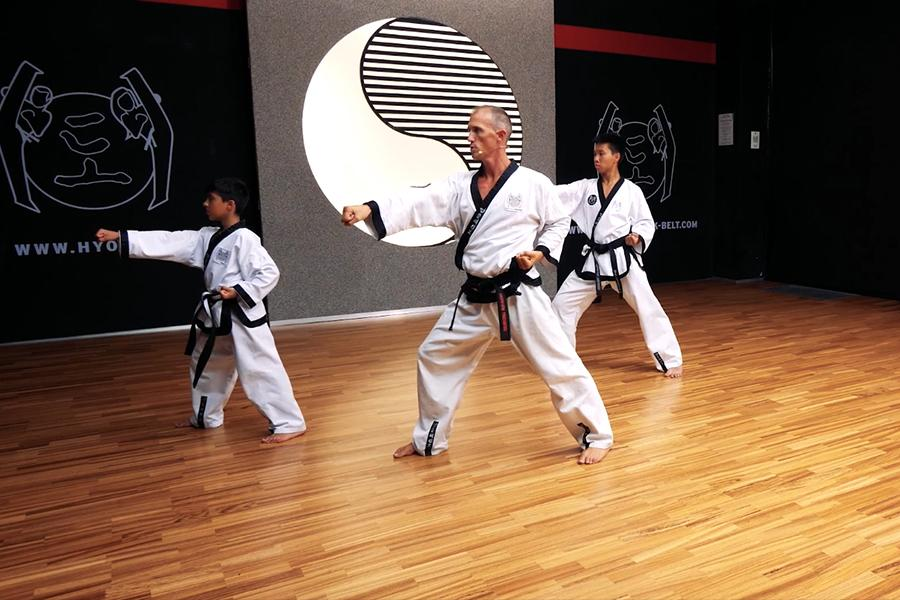 Zu sehen sind Dr. Andreas und zwei deiner Taekwondo-Schüler im Kampfanzug beim Ausüben eines Faustschlages.
