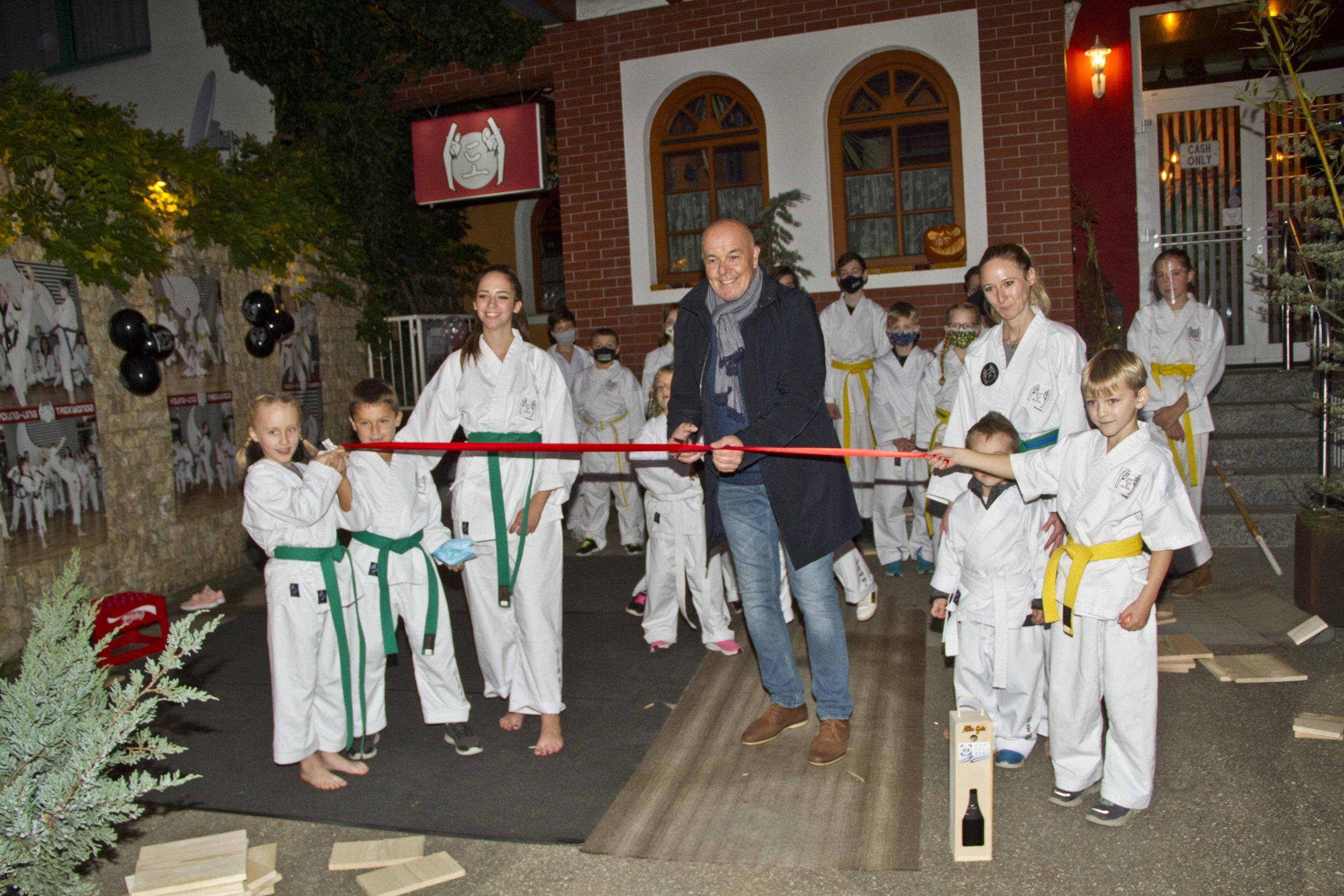 Taekwondo Gruppe -Bürgermeister zerschneidet rotes Band