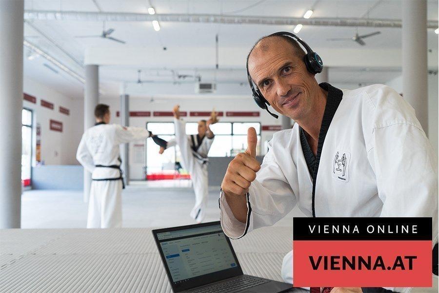 Mann mit Headset im Kampfanzug vor Laptop hält Daumen hoch