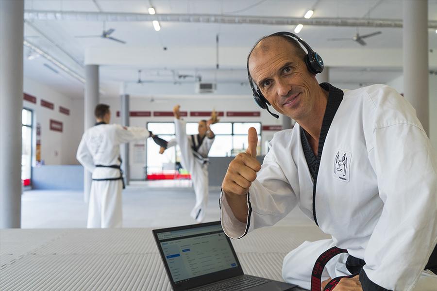 Im Vordergrund Dr. Andreas Held neben ihm ein Laptop, dahinter zwei Taekwondo-Schüler die Kicks üben.