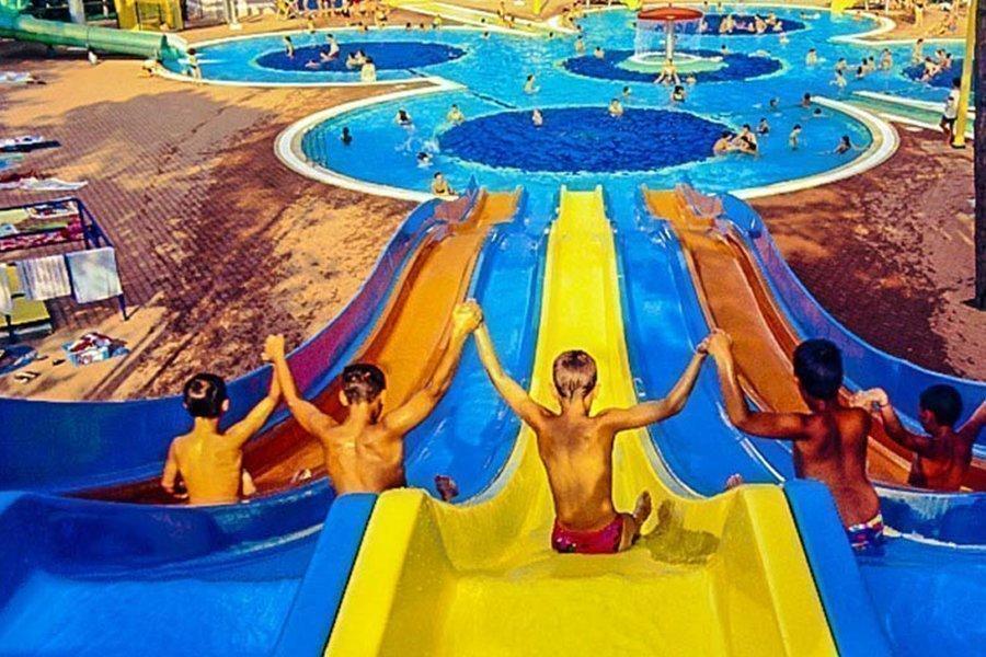 Kinder die bunte Wasserrutschen hinunter rutschen.