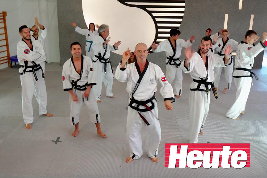 Männer und Frauen im Taekwondo-Kampfanzug tanzen in der Gruppe