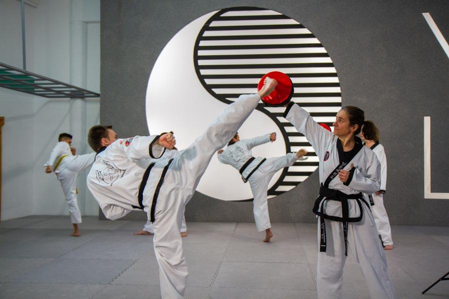 Erwachsene Taekwondo Schüler trainieren Kicks.
