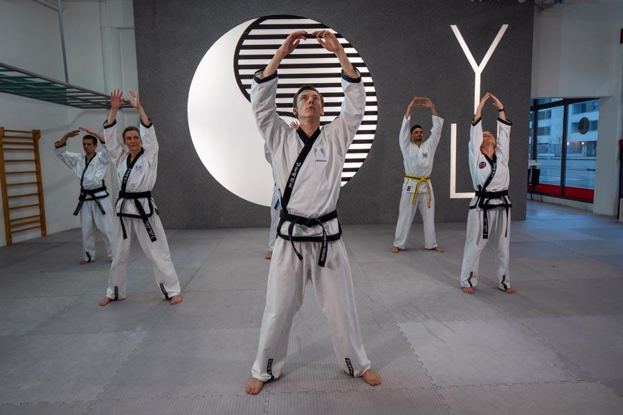 Taekwondo Meister macht Aufwärmübungen in einer kleinen Gruppe.