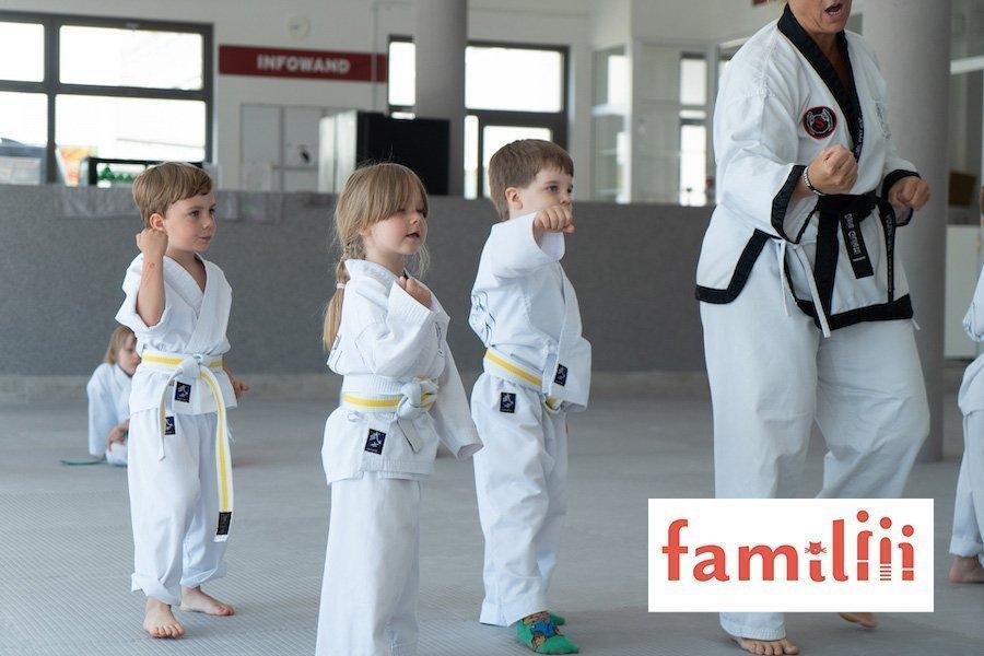 3 Kinder im weißen Taekwondo Anzug befinden sich Dojang mit Trainerin