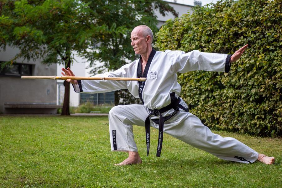 Älterer Mann im Kampfanzug trainiert im Grünen mit Stock Kimoodo.