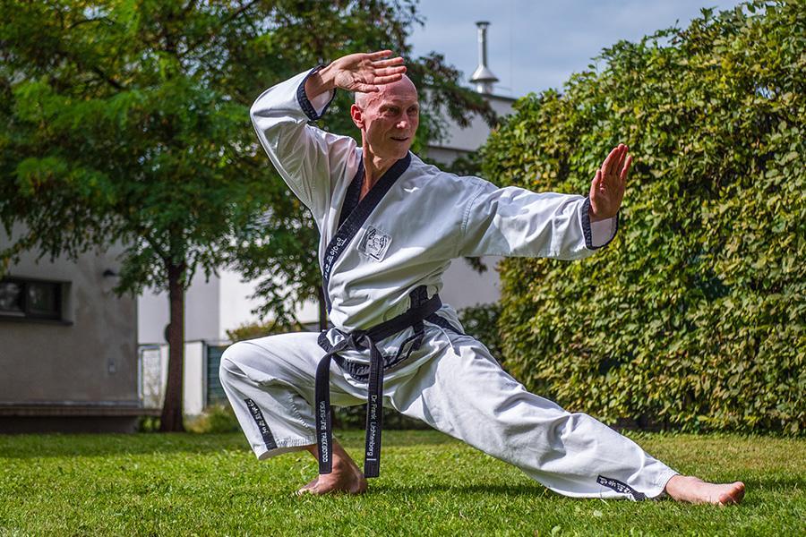 Älterer Mann im Kampfanzug trainiert im Grünen Kimoodo.