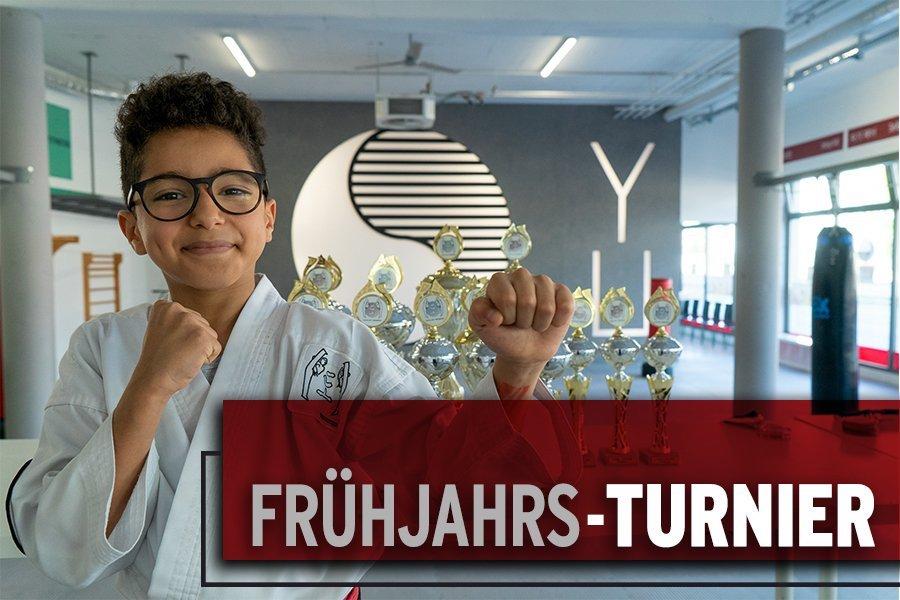 Junge mit Brille und Kampfanzug posiert vor einen Turm von Pokalen. Image Foto für unser Taekwondo Frühjahrs-Turnier