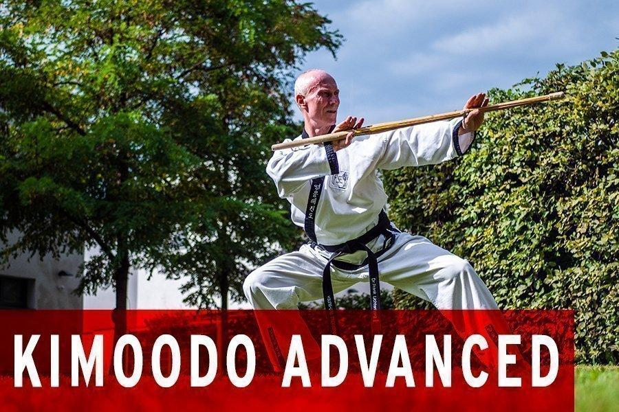 Mann im Kampfanzug im Freien mit einem Stock in Kimoode Pose.