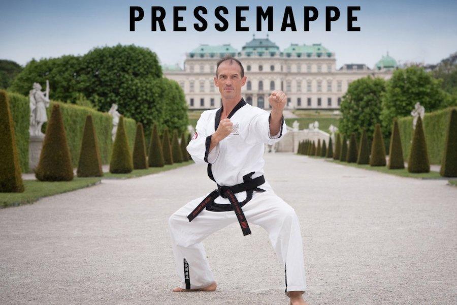 Mann steht im Kampfanzug in Kampfpose vor Schloss Schönbrunn.
