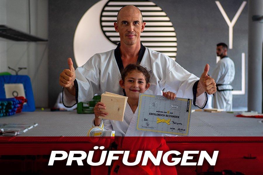 Dr. Andreas Held mit Taekwondomädchen. Sie hält eine Urkunde in der Hand und ein Bruchtest-Brett.