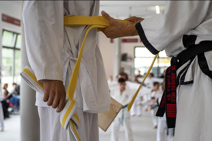 Umbinden von einem gelben Taekwondo-Gurt