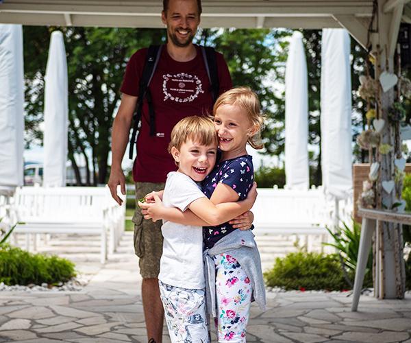 Junger Vater mit seinen beiden Kinder, die sich umarmen.