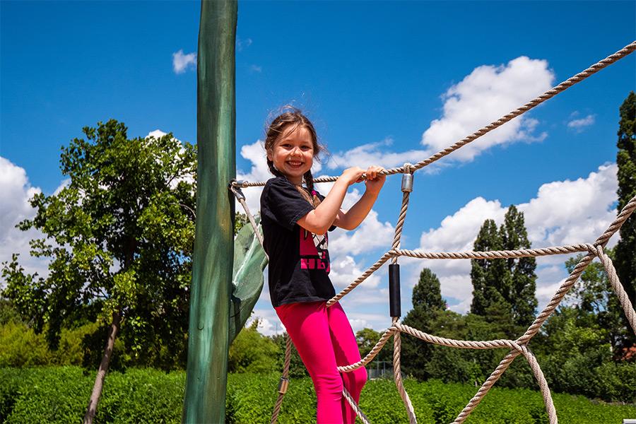 Junges Mädchen auf dem KLlettergerüst im Park