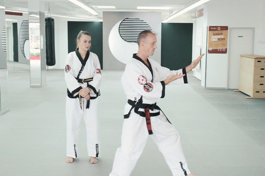 Dr. Andreas Held zeigt einer Taekwondo Schülerin die richtige Fußstellung bei den Hyongs.