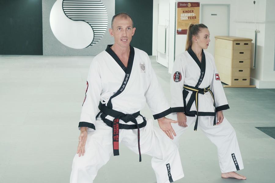 Dr. Andreas Held zeigt einer Taekwondo Schülerin die richtige Beinstellung bei den Hyongs.