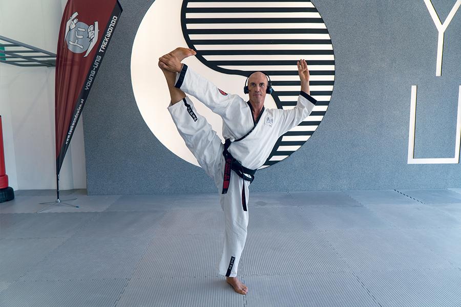 Dr. Andreas Held mit Headset, er steht und hält ein Bein gestreckt in der Luft.