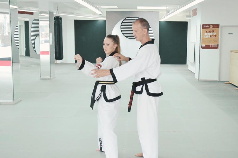 Dr. Andreas Held zeigt einer Taekwondo Schülerin die richtige Handstellung bei den Hyongs.