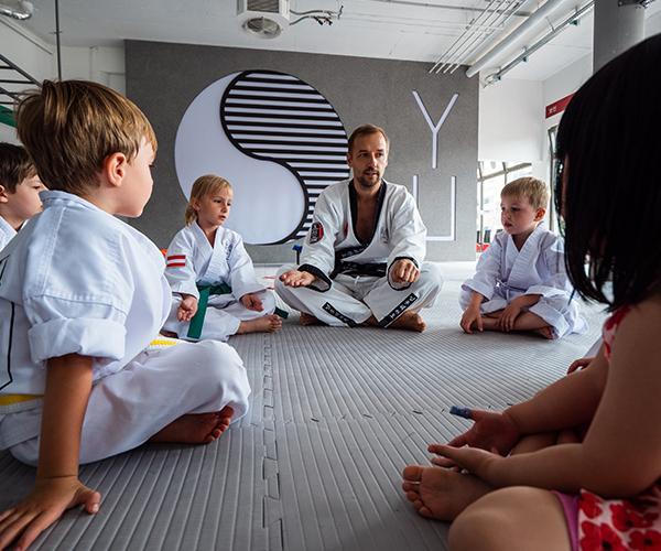 Taekwondo Trainer mit Kinder im Sitzkreis