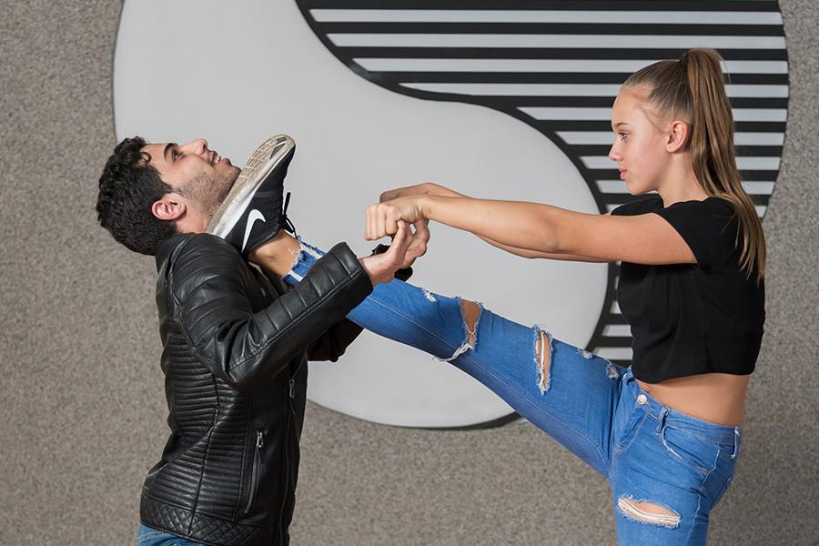 Teenager Mädchen kickt einen Angreifer weg.