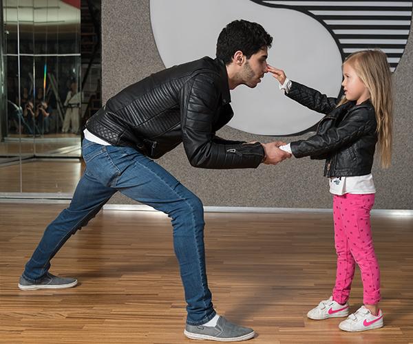 Kleines Mädchen verteidigt sich vor einem Angriff eines jungen Mannes