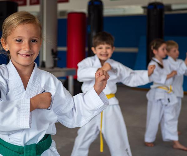 Kinder im Kampfanzug und Taekwondo-Pose im Dojang