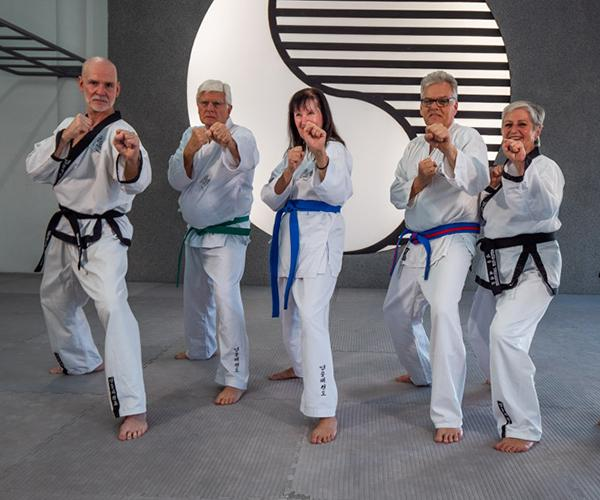 Gruppe von Senioren im Kampfanzug und Taekwondo Kampfstellung.