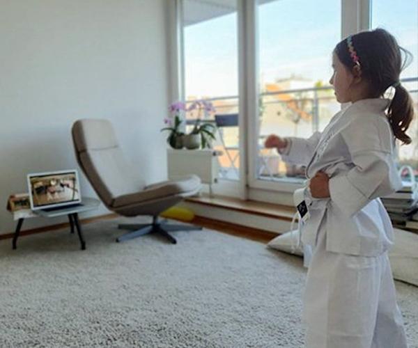 Mädchen trainiert im Wohnzimmer Taekwondo