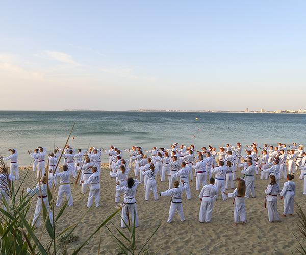 Eine Gruppe von menschen trainiert Taekwondo Training am Strand.