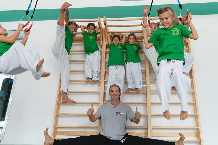 Kinder an der Spreossenwand mit Dr. Andreas Held im Spagat