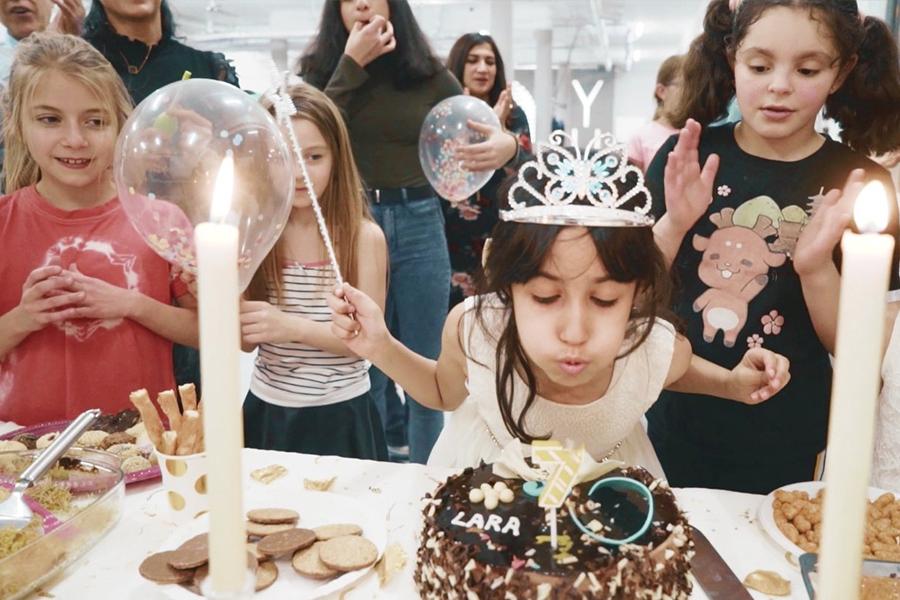 Junges Mädchen feiert ihren Geburtstag und bläst gerade die Kerzen aus.