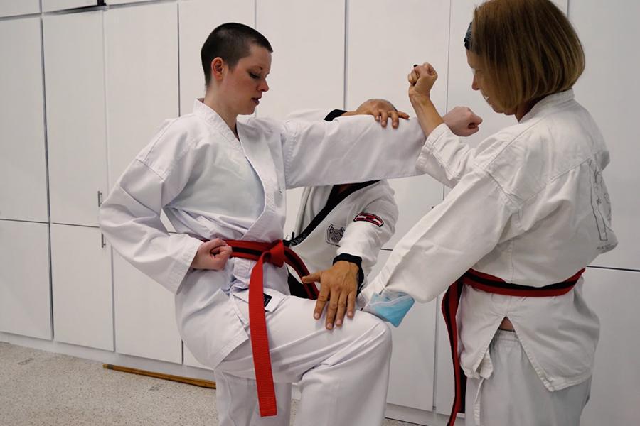 Dr. Andreas Held zeigt zwei Frauen im Kampfanzug die richtige Ausübung eines Kicks