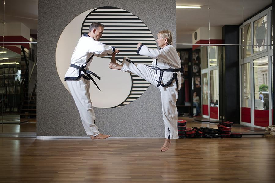 Ältere Dame trainiert Taekwondo Kicks mit dem Großmeister.