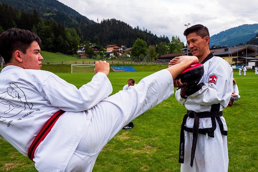 Teenager Bub trainiert Kicks mit Taekwondo Meister.