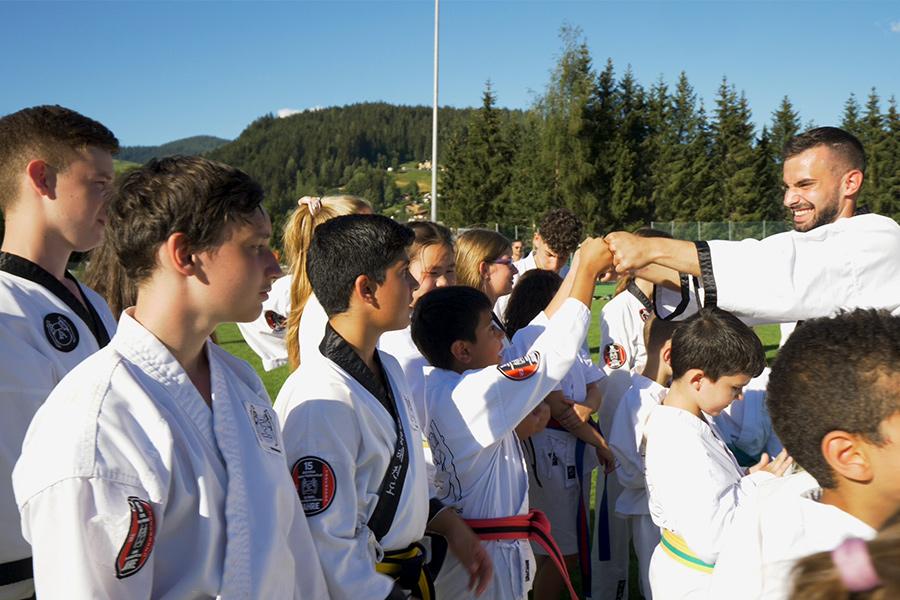 Taekwondo Meister beglückwünscht Kinder zur bestandenen Gurtprüfung.