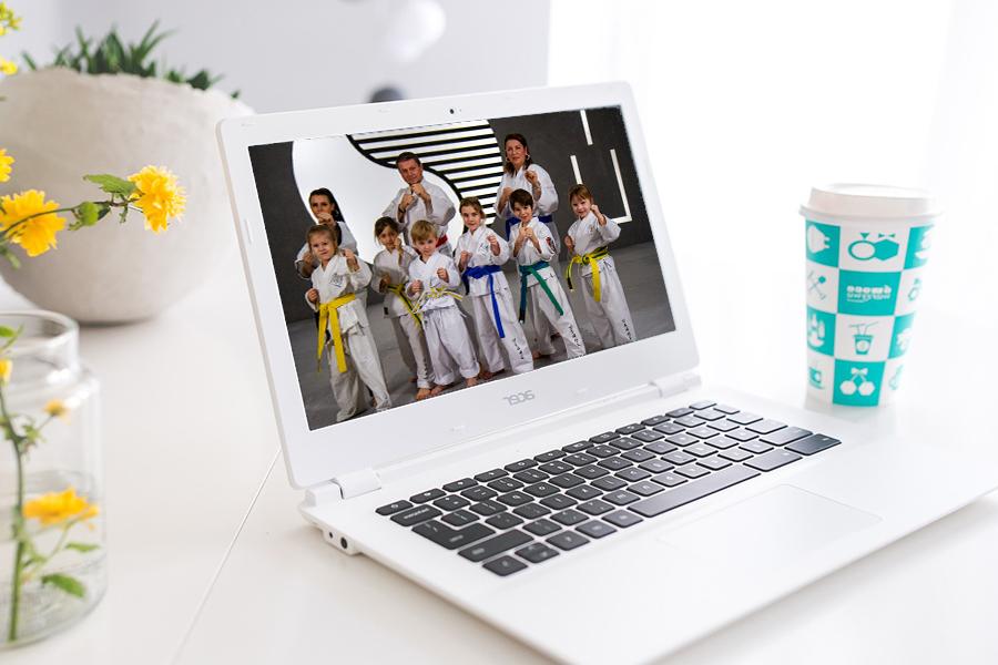 Laptop Bild zeigt Eltern mit ihren Kindern im Taekwondo Pose.