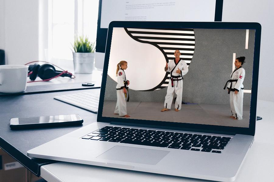 Aufgeschlagener Laptop mit einem Foto aus dem Family Concept. Zu sehen ist Dr. Andreas Held, ein junges Mädchen im Taekwondo Kampfanzug und eine Dame, die sich gegenüber stehen.