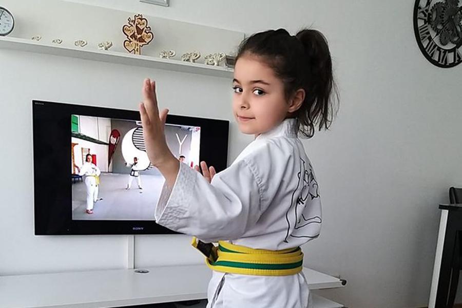 Mädchen im Kampfanzug trainiert zu Hause Taekwondo