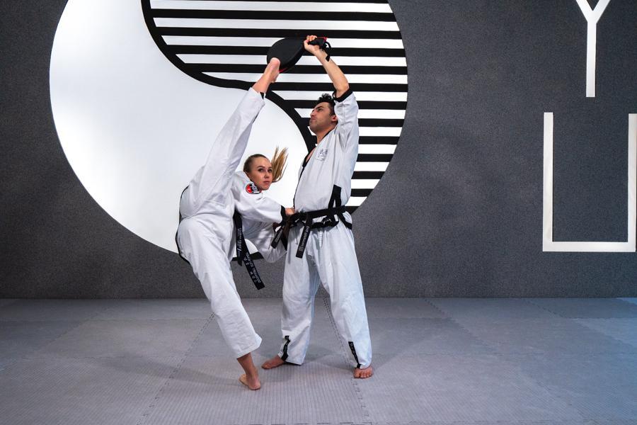 Teenager Mädchen kickt Handpratze die von einem Taekwondotrainer gehalten wird.