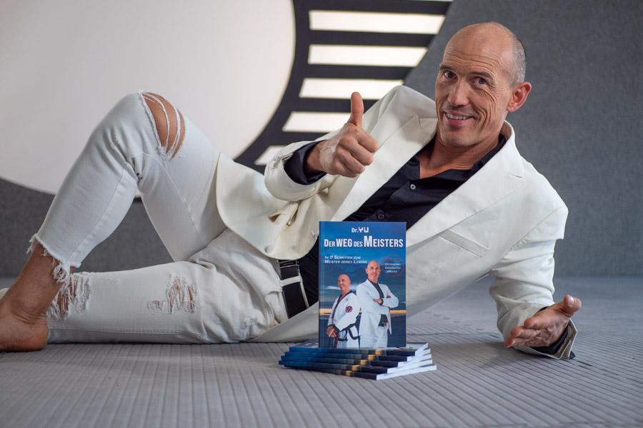 Mann im weißen Anzug liegt mit Büchern am Boden