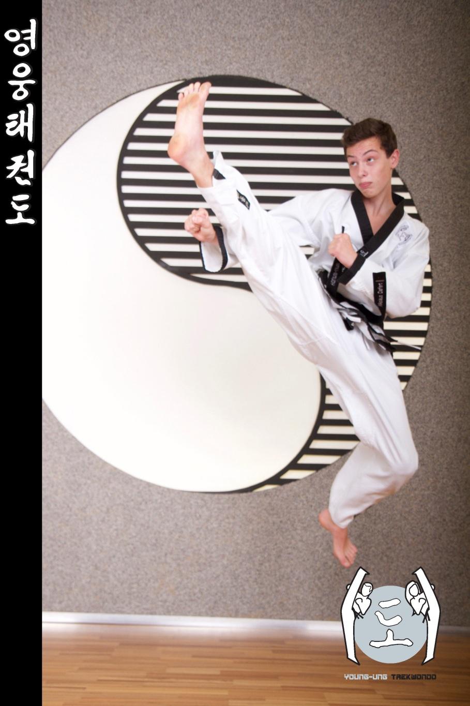 Junger Mann im Taekwondo Kampfanzug mit Schwarzgurt