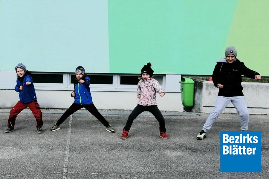 Drei Kinder und ein Erwachsener in Taekwondoposition